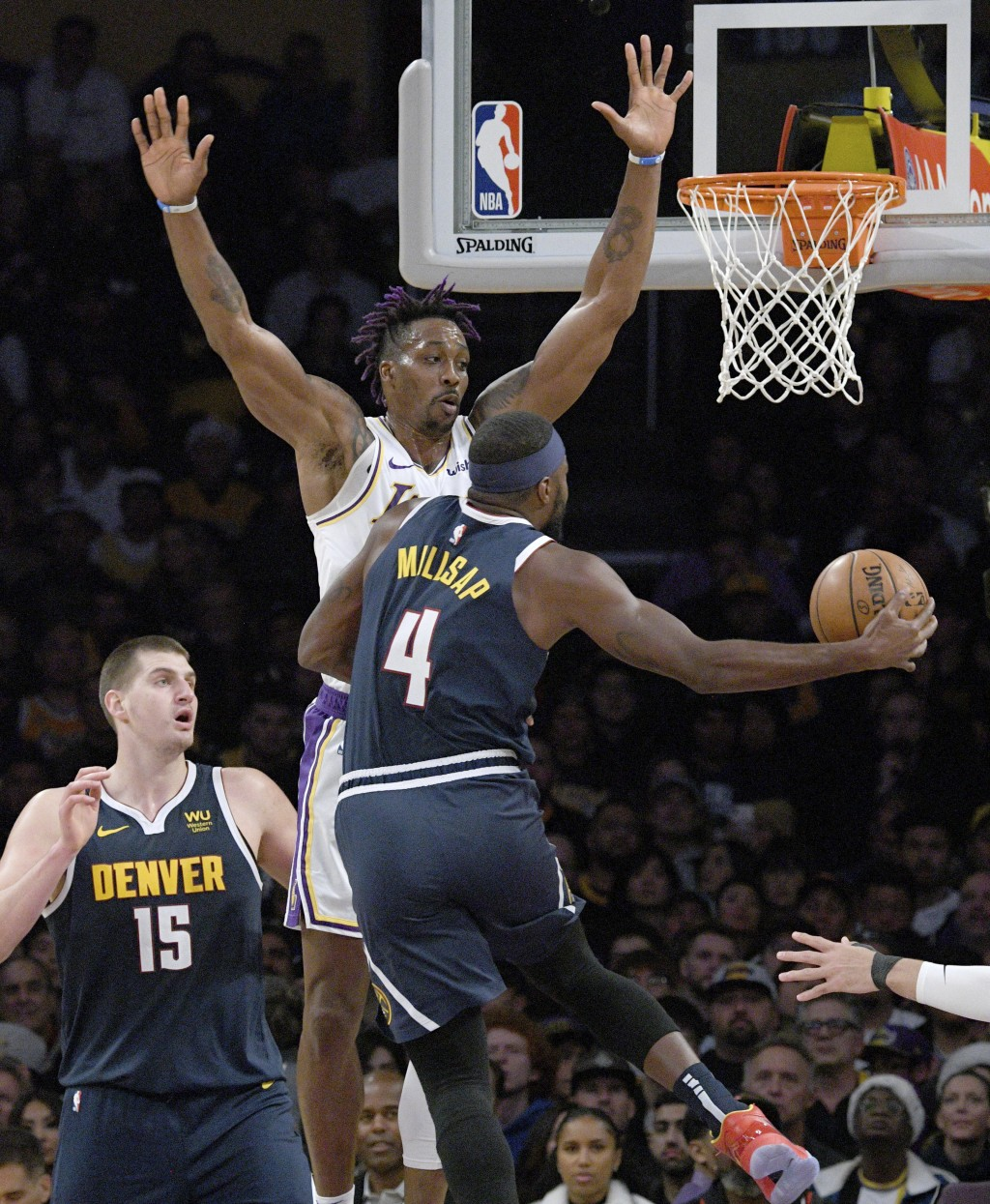 Los Angeles Lakers center Dwight Howard, center, defends the basket against Denver Nuggets forward Paul Millsap, right, during the first half of an NB...