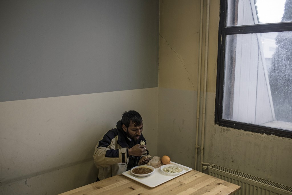 In this picture taken Thursday Dec. 12, 2019 a migrant from Afghanistan eats at a temporary reception centre set up by the IOM (International Organiza...