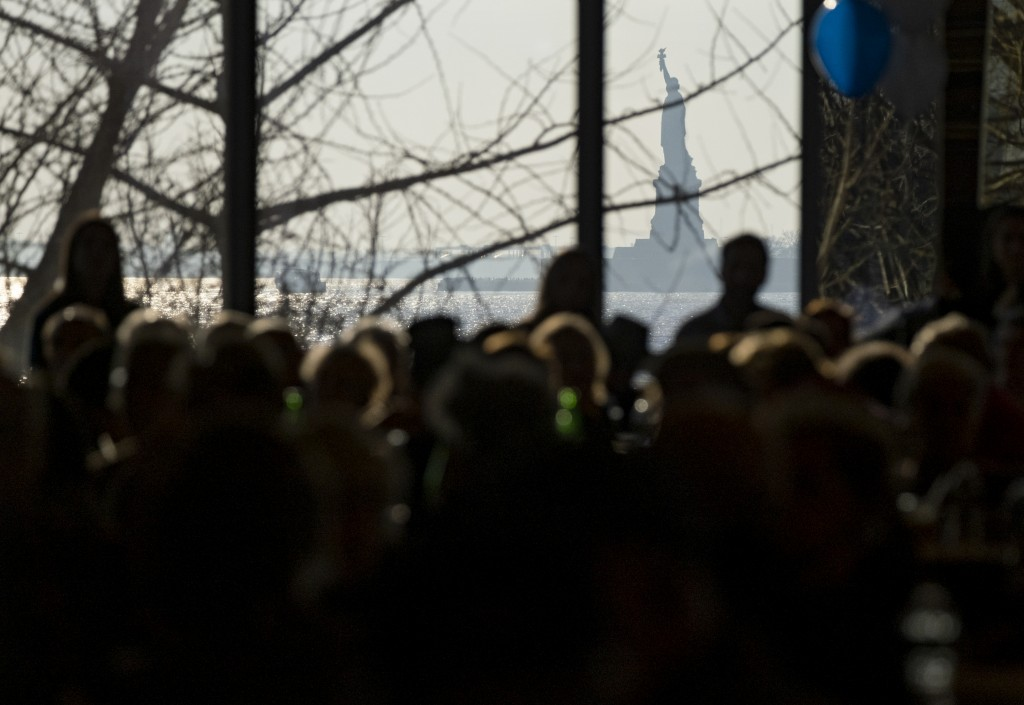 Survivors of the Holocaust and others gather at the Museum of Jewish Heritage as the Statue of Liberty can be seen through a window of the museum Sund...
