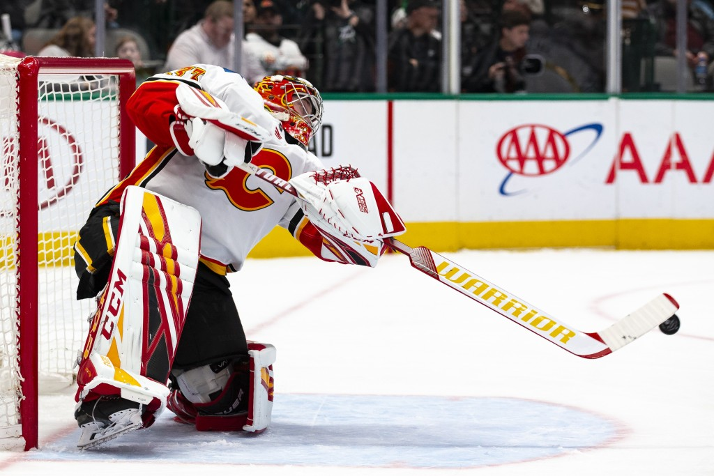 Calgary Flames goaltender David Rittich (33) plays the puck in front of his net during the first period of an NHL hockey game against the Dallas Stars...