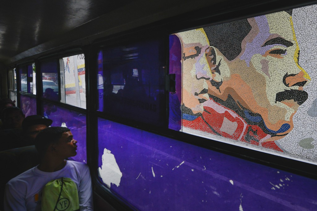 In this Dec. 19, 2019 photo, a man sitting on a bus looks at a mosaic of late leader Hugo Chavez, left, and of Venezuela's President Nicolas Maduro, r...