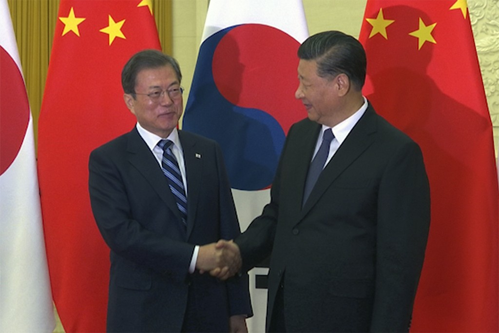 In this image from video, South Korean President Moon Jae-in, left, is great by his Chinese counterpart Xi Jinping ahead of their meeting at the Great...