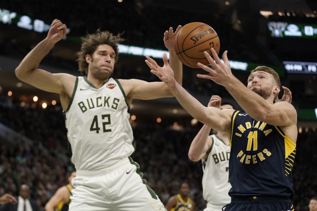 Indiana Pacers' Domantas Sabonis rebounds in front of Milwaukee Bucks' Robin Lopez during the first half of an NBA basketball game Sunday, Dec. 22, 20...