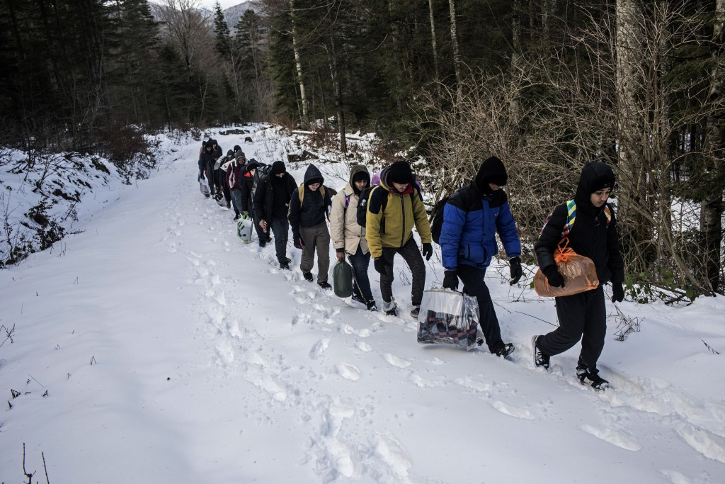 In this picture taken Sunday Dec. 15, 2019, a group of Egyptian migrants walk through the snow in a mountain area believed to be littered with landmin...