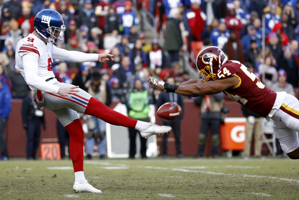Washington Redskins linebacker Nate Orchard, right, blocks a punt attempt by New York Giants punter Riley Dixon during the second half of an NFL footb...