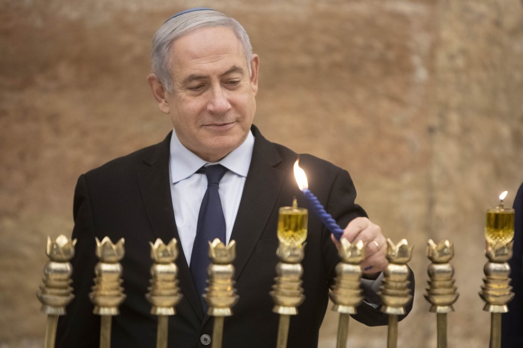 Israeli Prime Minister Benjamin Netanyahu, lights a Hanukkah candle at the Western Wall, the holiest site where Jews can pray in Jerusalem's old city,...