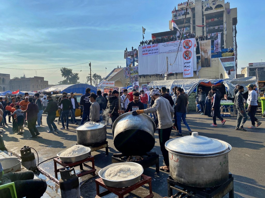 Volunteers prepare free food while anti-government protesters gather in Tahrir Square in Baghdad, Iraq, Sunday, Dec. 22, 2019. Thousands of protesters...