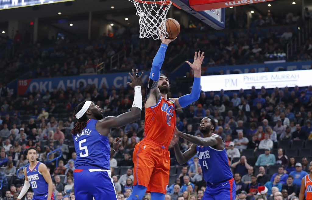 Oklahoma City Thunder center Steven Adams (12) goes up for a basket between Los Angeles Clippers forward Montrezl Harrell (5) and forward JaMychal Gre...