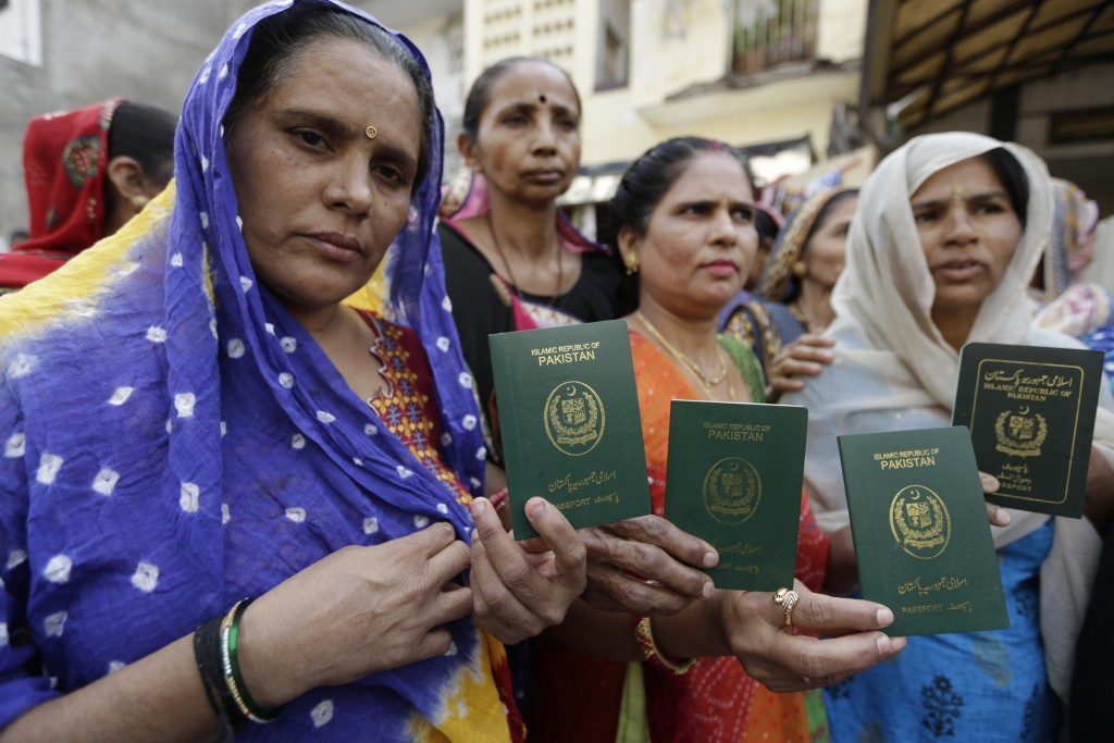 Hindu refugees who migrated from Sindh province of Pakistan display their passports as they support the Citizenship Amendment Act in Ahmadabad, India,...