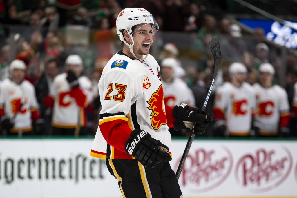 Calgary Flames center Sean Monahan (23) smiles after left wing Matthew Tkachuk (19) scores a goal during the second period of an NHL hockey game again...