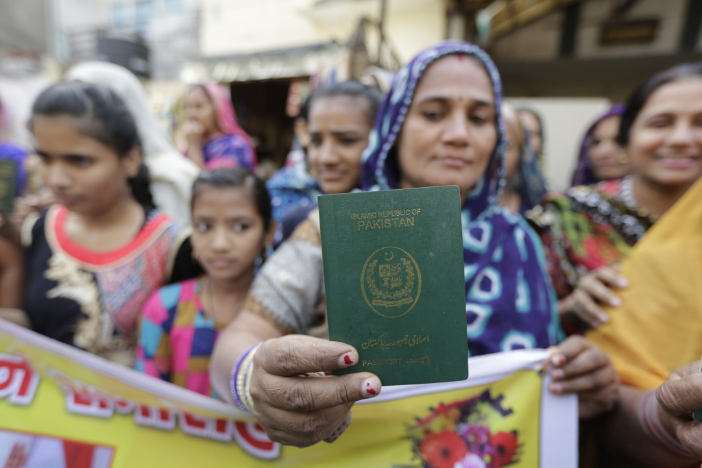 A Hindu refugee who migrated from Sindh province of Pakistan displays her passport as she along with others support the Citizenship Amendment Act in A...