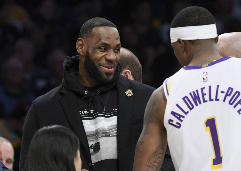 Los Angeles Lakers guard LeBron James, left, talks with guard Kentavious Caldwell-Pope during the first half of an NBA basketball game against the Den...