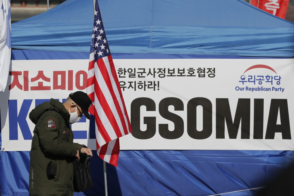 FILE - In this Nov. 22, 2019, file photo, a man stands near the banner demanding to keep the General Security of Military Intelligence Agreement, or G...
