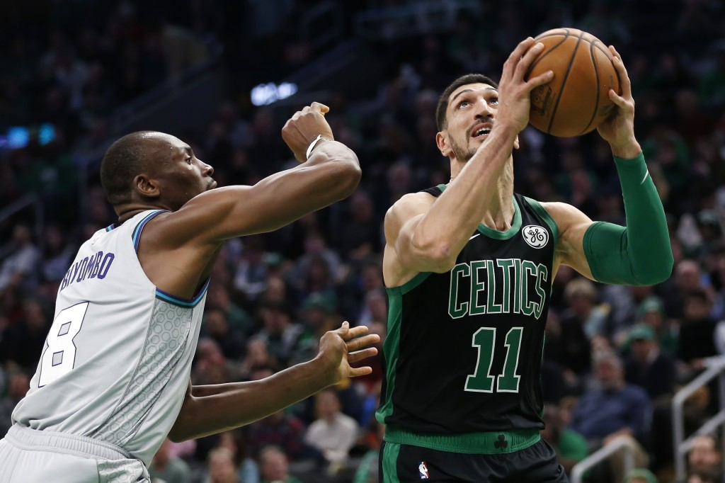 Boston Celtics' Enes Kanter (11) shoots against Charlotte Hornets' Bismack Biyombo (8) during the first half of an NBA basketball game in Boston, Sund...