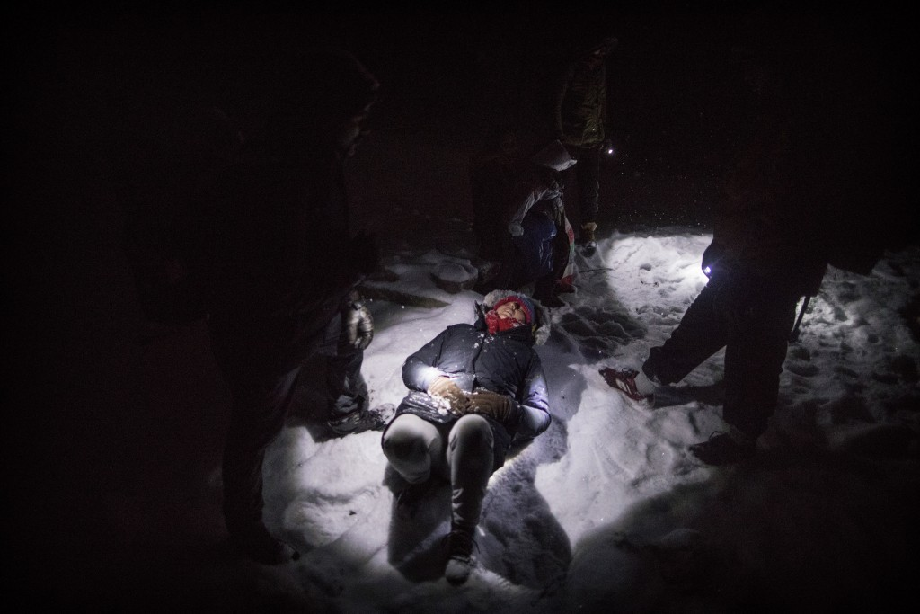 In this picture taken Thursday Dec. 12, 2019, Indian migrant Nishademi, 22, lies exhausted on the snow near the Croatian border as a group of migrants...
