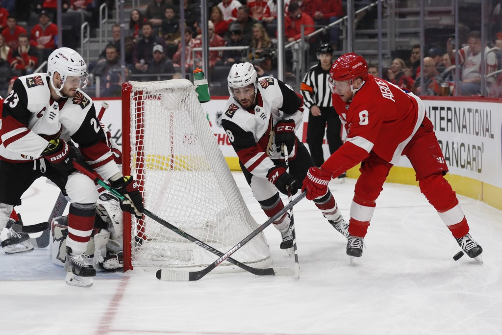 Detroit Red Wings left wing Justin Abdelkader (8) loses control the puck as Arizona Coyotes defenseman Oliver Ekman-Larsson (23) and center Nick Schma...