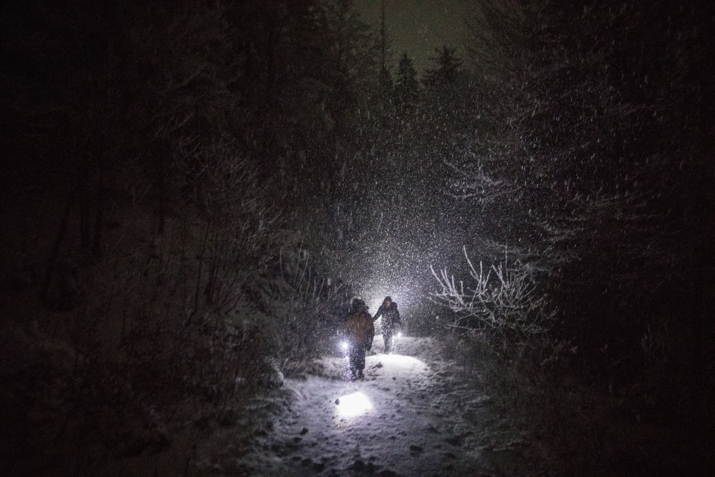 In this picture taken Thursday Dec. 12, 2019, a group of Syrian refugees walk their way under a blizzard as they attempt to enter the EU through Croat...