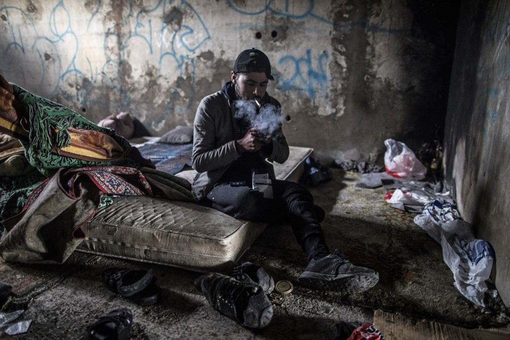 In this picture taken Saturday Dec. 14, 2019, Syrian refugee from Idlib province Mohhamed, 19, lights up a cigarette after breakfast inside an abandon...