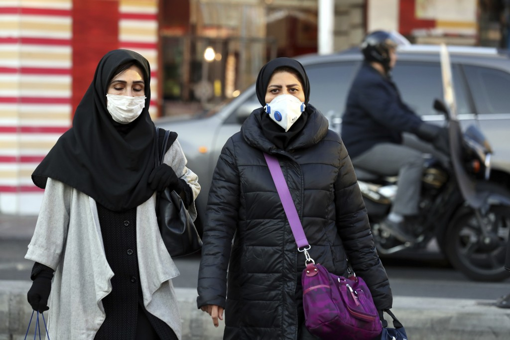 People wear masks to help guard against dangerous levels of air pollution in Tehran, Iran, Monday, Dec. 23, 2019. Poor air quality forced Iran's gover...
