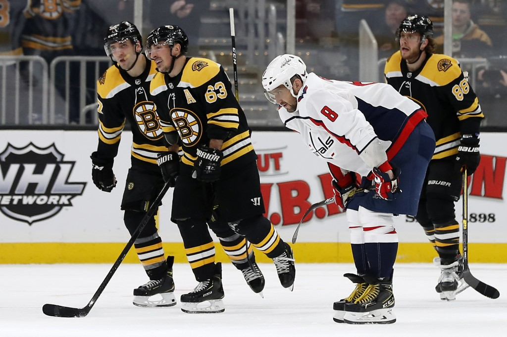 Washington Capitals' Alex Ovechkin bends over as Boston Bruins' Brad Marchand (63) leads teammates David Pastrnak (88) and Patrice Bergeron to the ben...