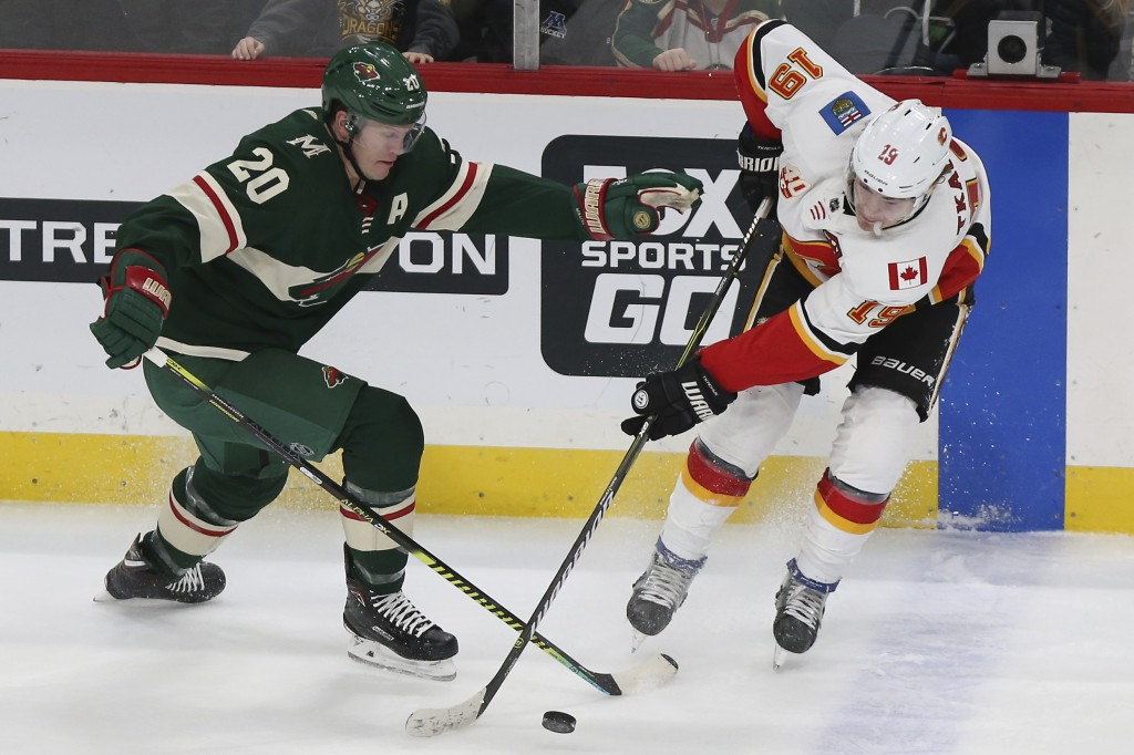 Minnesota Wild's Ryan Suter and Calgary Flames' Matthew Tkachuk go after the puck in the third period of an NHL hockey game Monday, Dec. 23, 2019, in ...