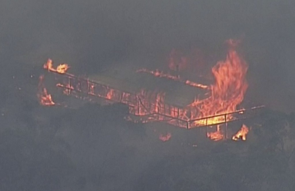 This image made from video shows a house on fire from a bushfire, Monday, Dec. 23, 2019, in Gumeracha, South Australia. Australia's embattled prime mi...