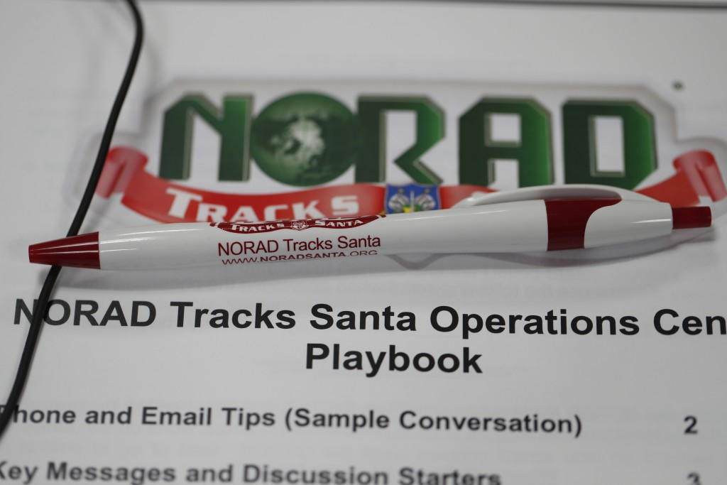 A pen rests on the playbook for volunteers who will be taking calls from around the globe in the NORAD Tracks Santa center at Petserson Air Force Base...