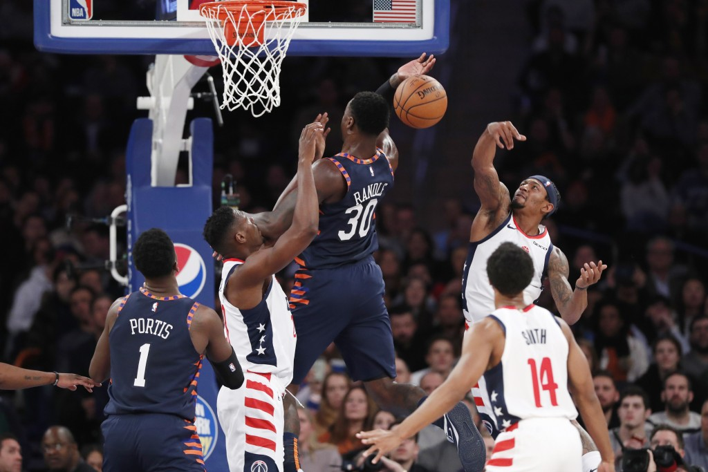 Washington Wizards'Bradley Beal, upper right, knocks the ball from the hands of New York Knicks forward Julius Randle (30) during the first half of an...