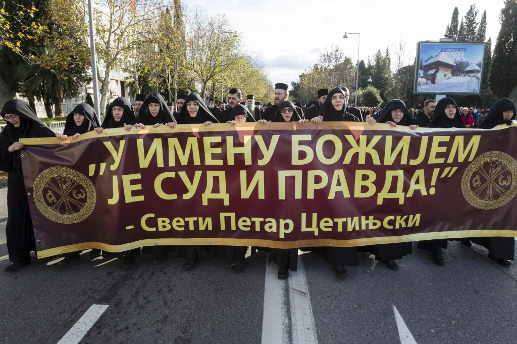 Serbian Orthodox Church clergy in Montenegro march and hold a banner reading: ''Judgment and Justice are in God's name'' as they protest the planned a...