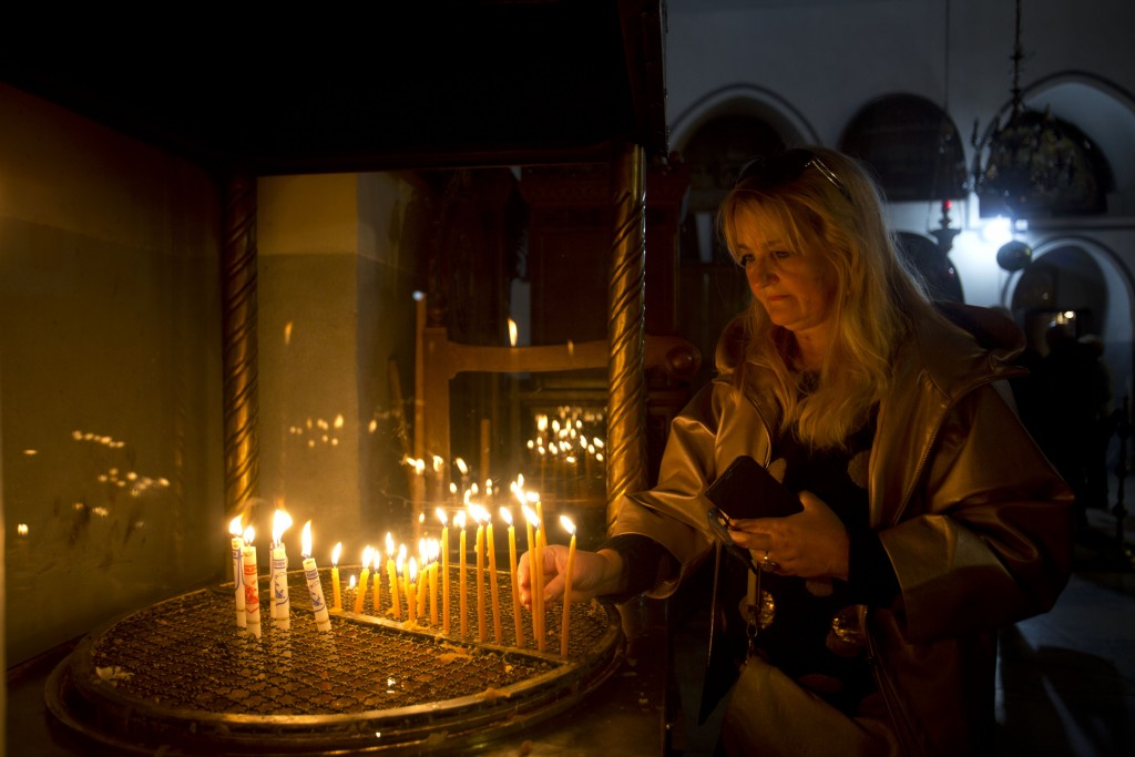 A visitor lights a candle at the Church of the Nativity built on top of the site where Christians believe Jesus Christ was born on Christmas Eve, in t...