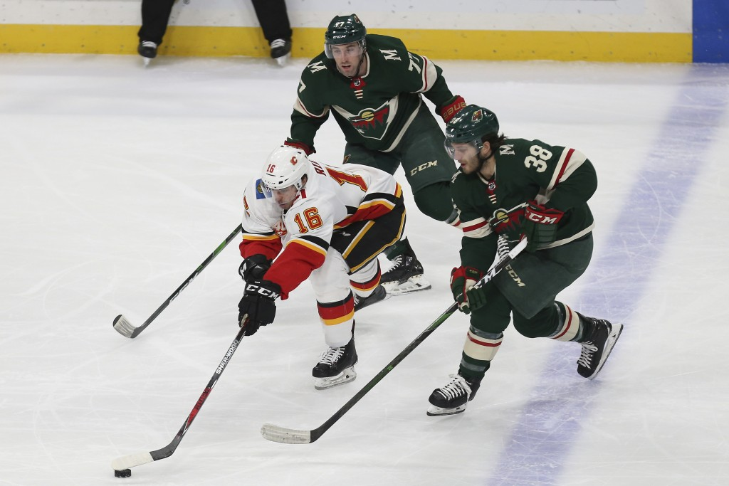 Calgary Flames' Tobias Rieder of Germany controls the puck against Minnesota Wild's Ryan Hartman (38) and Brad Hunt (77) in the first period of an NHL...