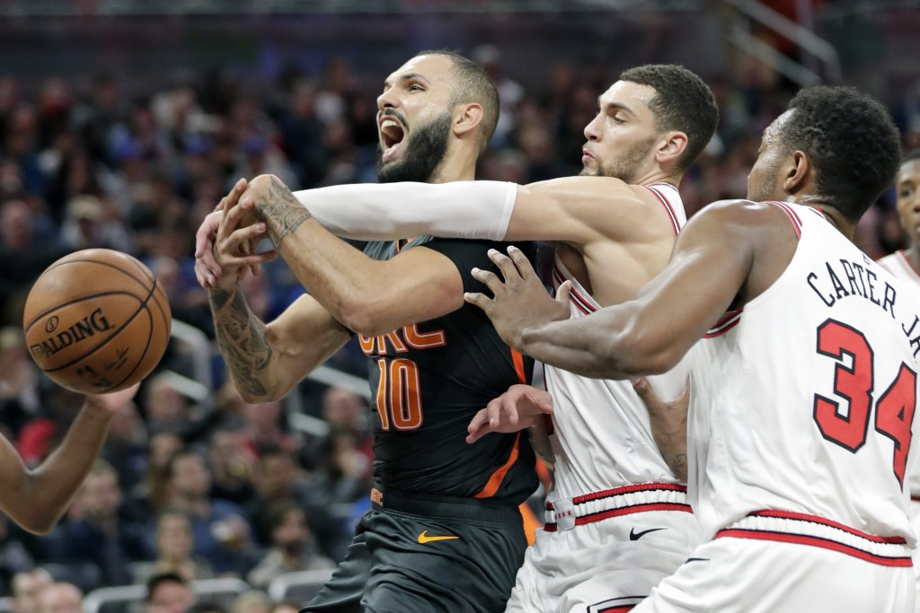 Orlando Magic guard Evan Fournier, left, is fouled as he goes up for a shot against Chicago Bulls guard Zach LaVine, center, and center Wendell Carter...