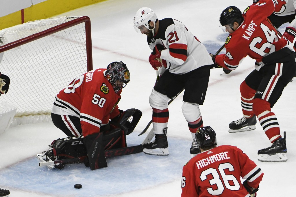 Chicago Blackhawks goaltender Corey Crawford (50) makes a save on New Jersey Devils right wing Kyle Palmieri (21) during the second period of an NHL h...