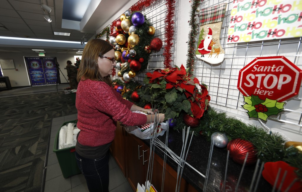 Volunteer Nicole Schreiner places a display of poinsettias in the NORAD Tracks Santa center at Peterson Air Force Base, Monday, Dec. 23, 2019, in Colo...