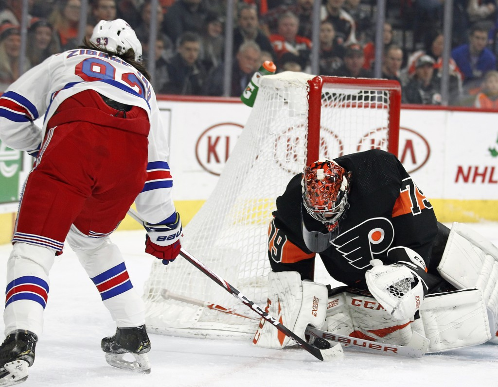 The shot on goal by New York Rangers' Mika Zibanejad, left, is stopped by Philadelphia Flyers' Carter Hart during the first period of an NHL hockey ga...