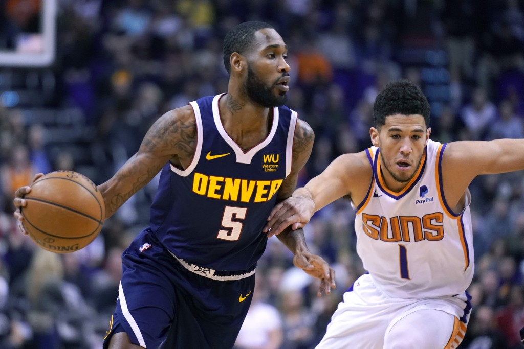 Denver Nuggets guard Will Barton (5) drives past Phoenix Suns guard Devin Booker in the first half of an NBA basketball game, Monday, Dec. 23, 2019, i...