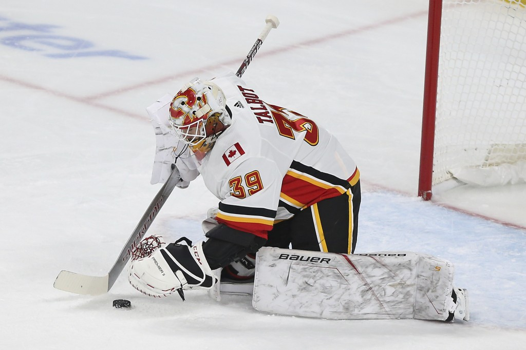 Calgary Flames' goalie Cam Talbot stops the puck against the Minnesota Wild in the first period of an NHL hockey game Monday Dec. 23, 2019, in St. Pau...