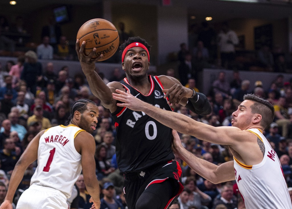 Toronto Raptors guard Terence Davis (0) drives the ball past the defense of Indiana Pacers guard T.J. McConnell (9) during an NBA basketball game, Mon...