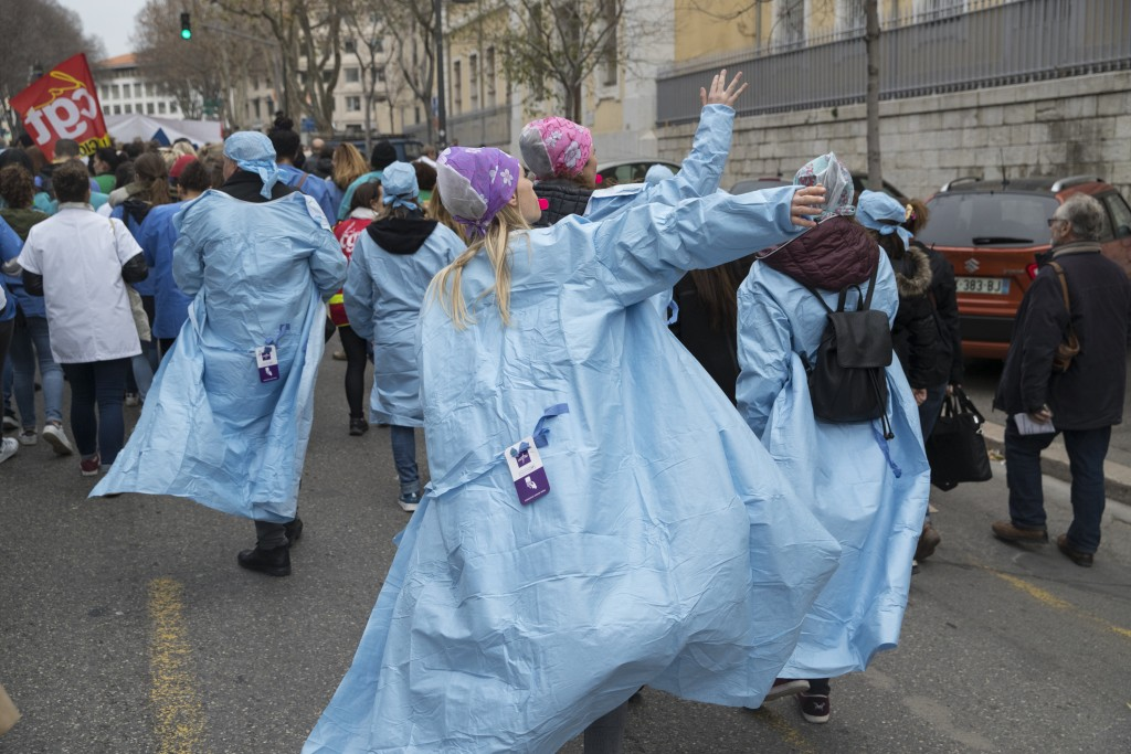 In this photo taken Tuesday Dec.17, 2019 Hospital workers march in Marseille, southern France. In a hospital in Marseille, student doctors are holding...