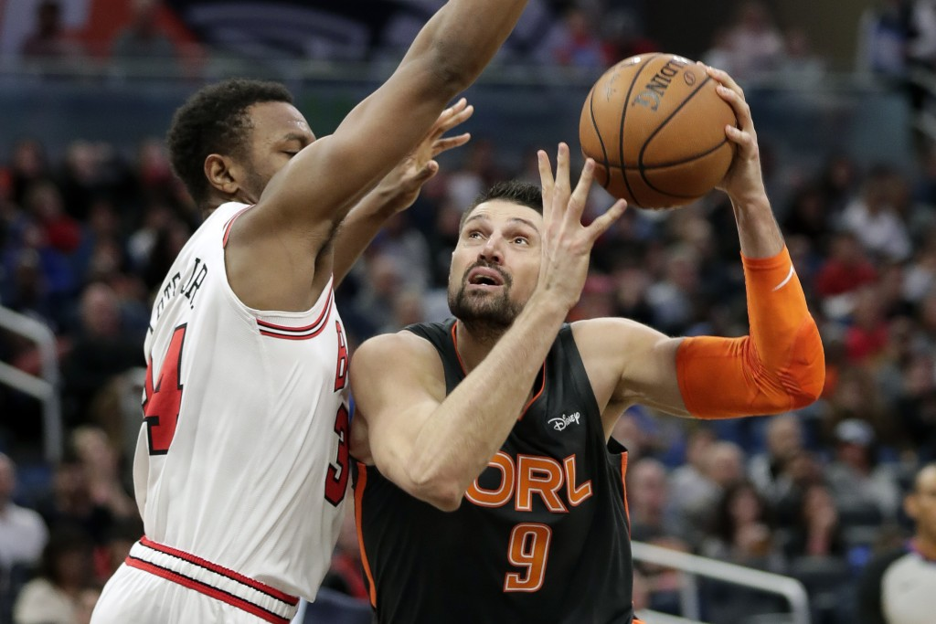 Orlando Magic center Nikola Vucevic (9) goes up for a shot against Chicago Bulls center Wendell Carter Jr. during the second half of an NBA basketball...