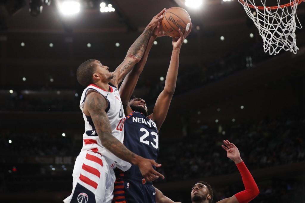 Washington Wizards guard Gary Payton II (20) blocks New York Knicks center Mitchell Robinson (23) during the second half of an NBA basketball game in ...