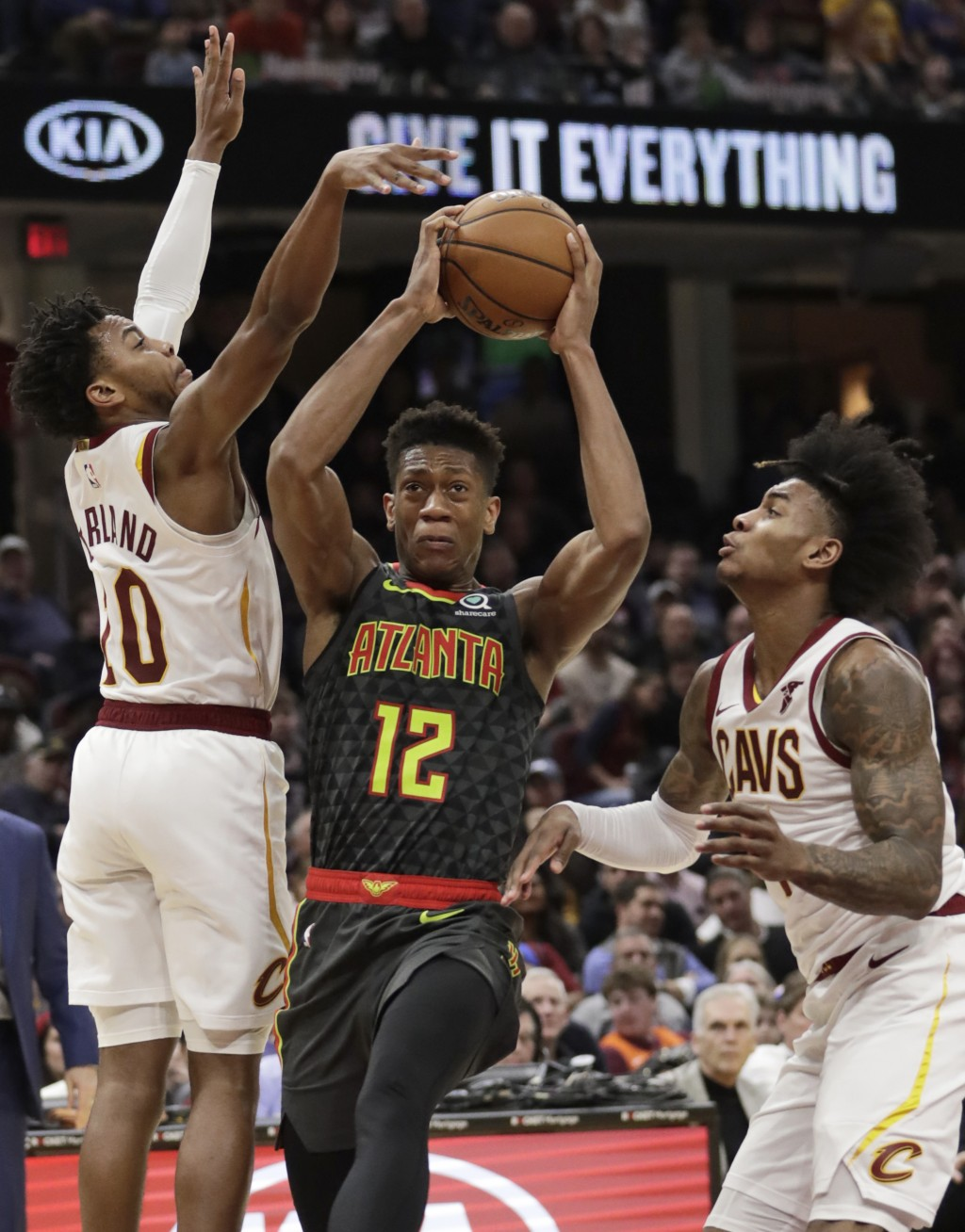 Atlanta Hawks' De'Andre Hunter (12) drives between Cleveland Cavaliers' Darius Garland (10) and Kevin Porter Jr. during the second half of an NBA bask...