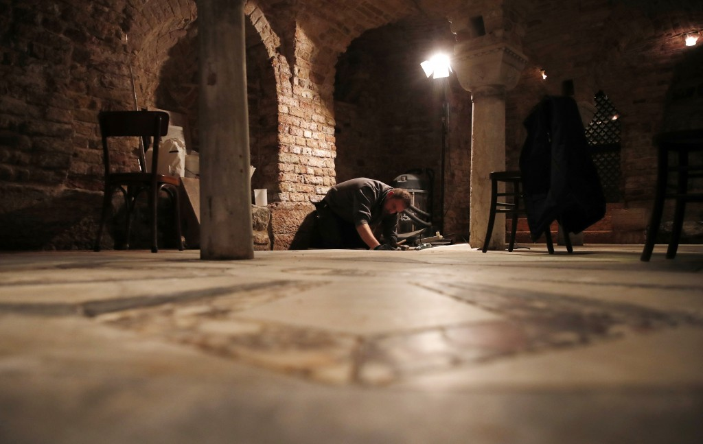 A man works in the St. Mark's Basilica crypt in Venice, Italy, Tuesday, Dec. 17, 2019.  Still invisible to the naked eye and the casual visitors, rece...