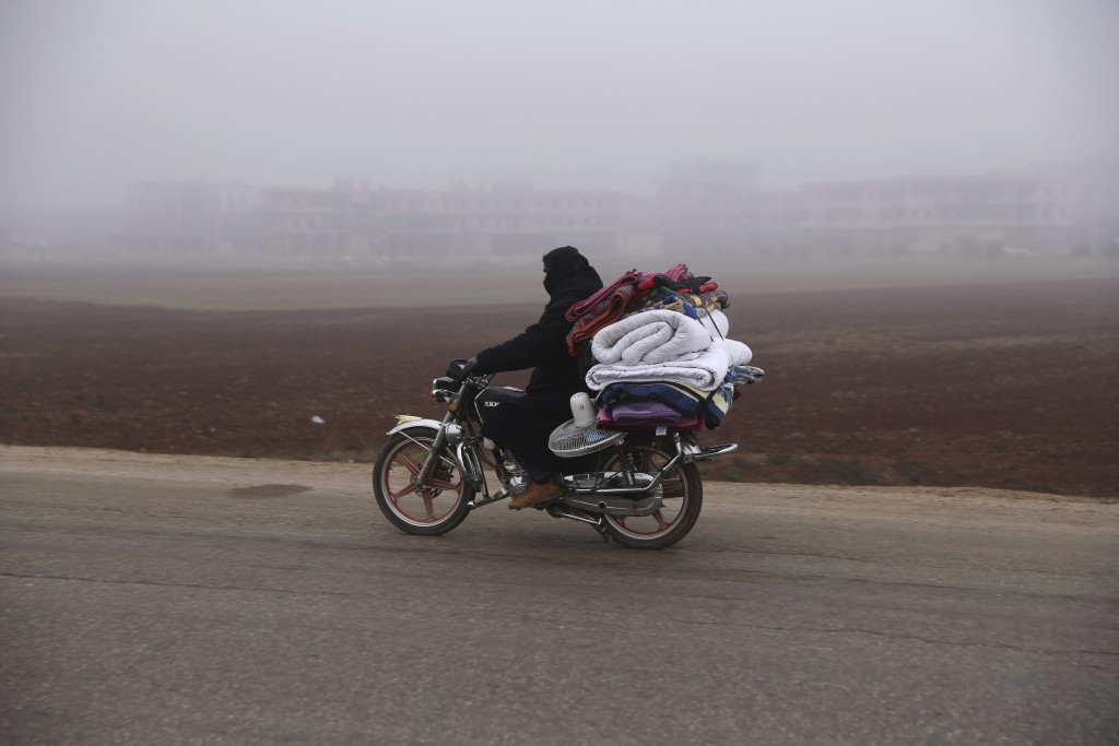 A man carries household goods on a motorbike while fleeing Maaret al-Numan, Syria, ahead of a government offensive, Monday, Dec. 23, 2019. (AP Photo/G...