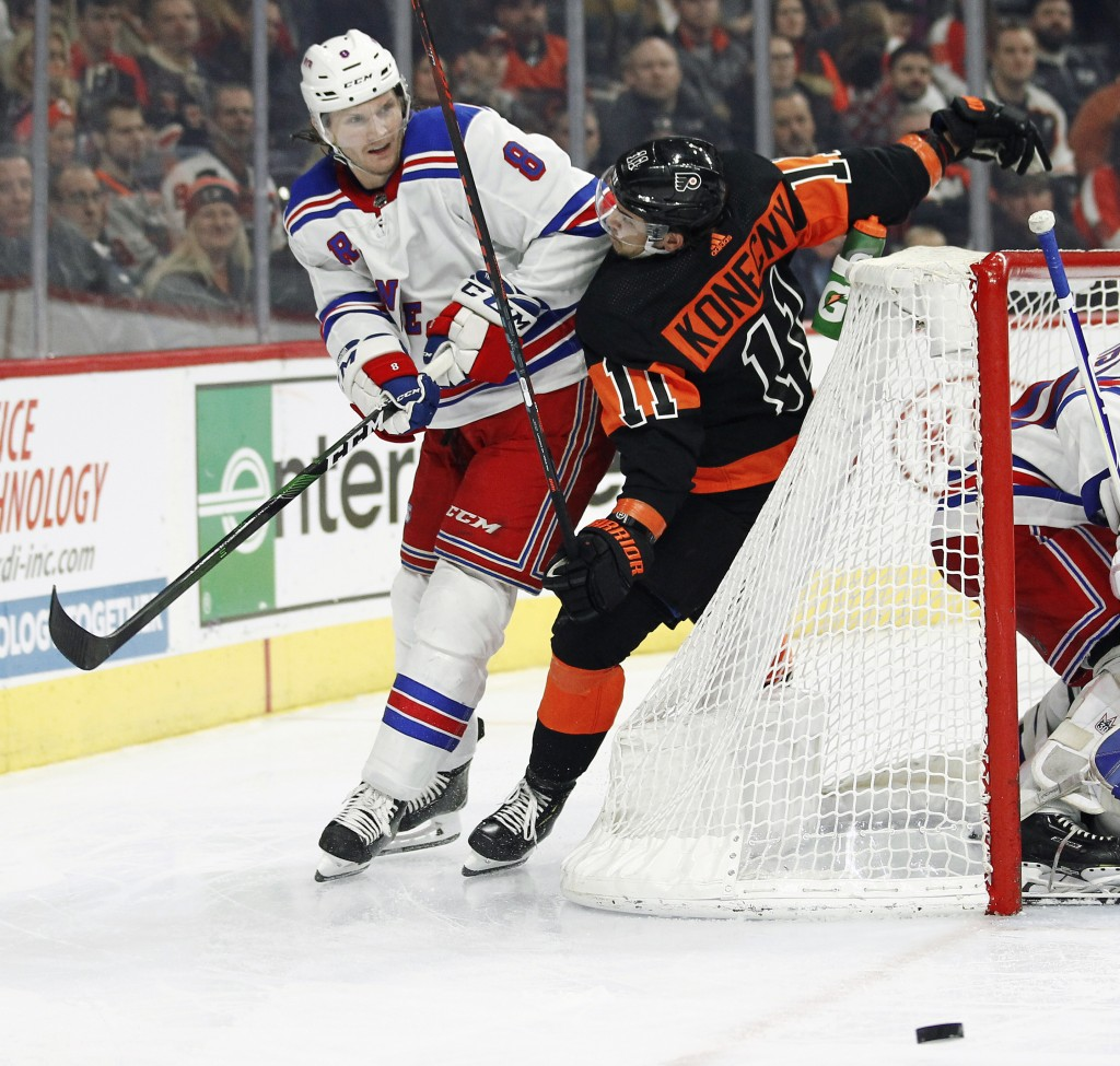 New York Rangers' Jacob Trouba shoves Philadelphia Flyers' Travis Konecny into the net as the two chase the puck during the second period of an NHL ho...