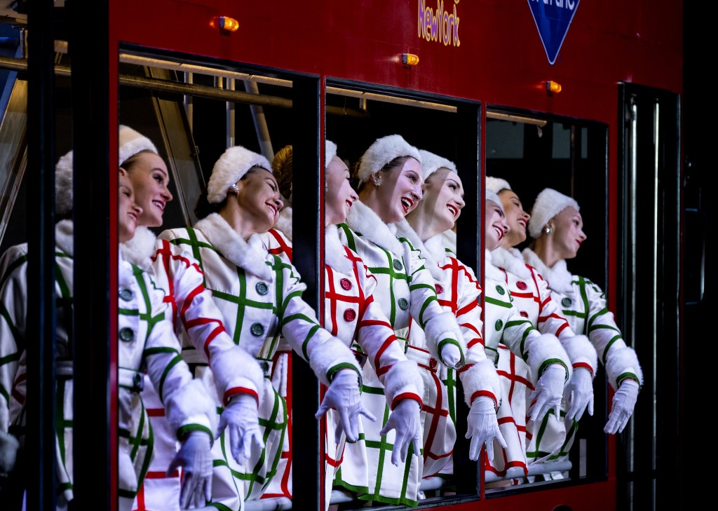 """In this Monday, Nov. 25, 2019 photo, Rockette Sydney Mesher, fifth from right, rides a depiction of a sightseeing bus during a performance of """"New Yor..."""