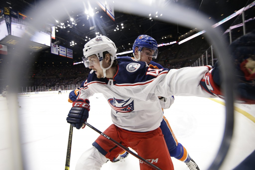 Columbus Blue Jackets' Dean Kukan, left, fights for position with New York Islanders' Michael Dal Colle during the second period of an NHL hockey game...
