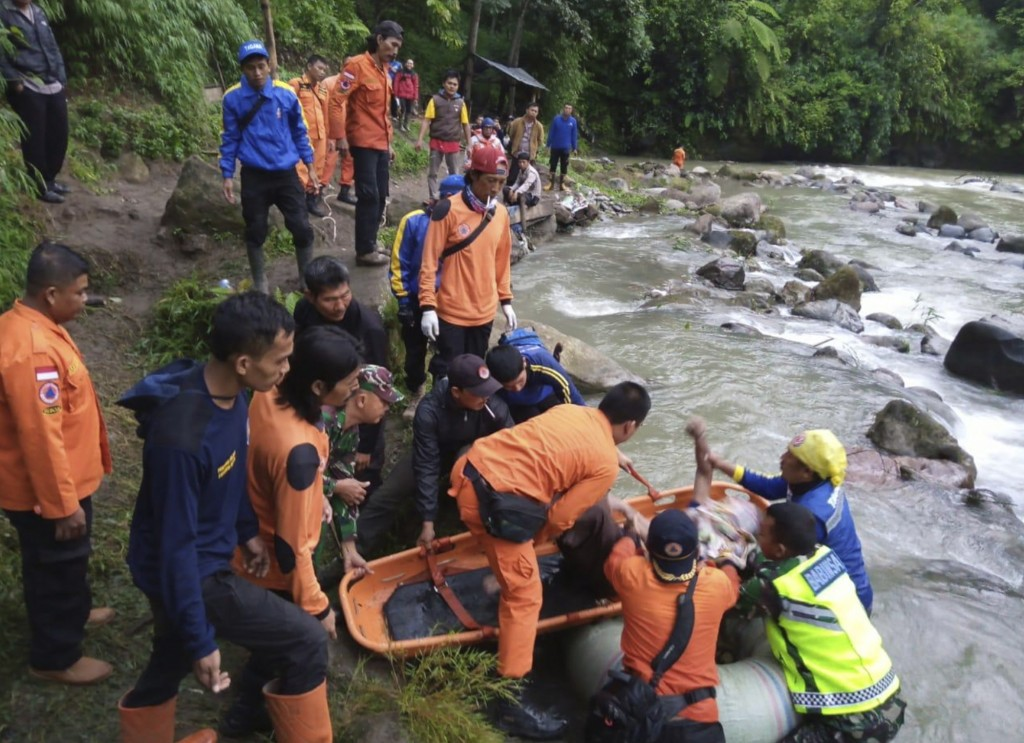 In this photo released by the National Search And Rescue Agency (BASARNAS), rescuers remove the body of a victim of a bus accident in Pagaralam, Indon...
