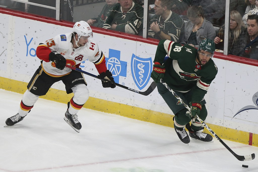 Minnesota Wild's Jordan Greenway and Calgary Flames' Sean Monahan go after the puck in the first period of an NHL hockey game Monday Dec. 23, 2019, in...
