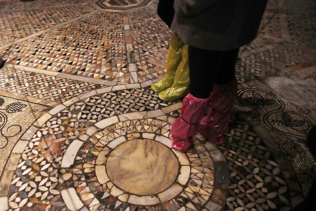 People walk on an interior mosaic floor of the St. Mark's Basilica in Venice, Italy, Tuesday, Dec. 17, 2019.  Still invisible to the naked eye and the...